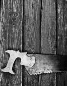 Old rusty saw on wooden background, bw photo  — Stock Photo