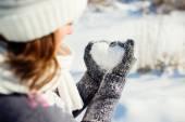 Молодые женщины, держит сердце в форме снега в руках — Стоковое фото