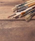 Set of paintbrushes on a wood background, tinted photo — Stock Photo