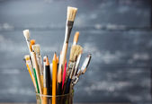 Photo of paint brushes in a glass standing on old wooden table,  — Stok fotoğraf