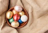 Golden and red Easter eggs in wooden plate — Stock Photo