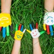 Colored hands with smile painted in colorful paints against gree — Stock Photo #76790439