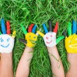 Colored hands with smile painted in colorful paints against gree — Stock Photo #76790561