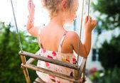 Šťastná dívka baví na houpačce na letní den — Stock fotografie