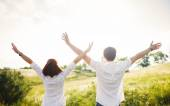 Couple standing in the field hands up, summer outdoor — Stock Photo
