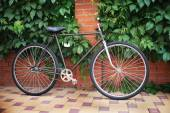 Old style singlespeed bicycle against brick wall, tinted photo — Stock Photo