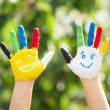 Colored hands with smile painted in colorful paints against gree — Stock Photo #76804709