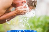 A man refreshes himself with a splash of cool, fresh water on hi — Stock Photo