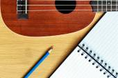 Ukulele guitar with  notebook and pencil  — Stock Photo