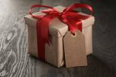 Rustic gift box with red ribbon bow and empty tag — Stock Photo