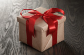 Rustic gift box with red ribbon bow — Stock Photo