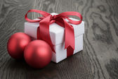 Gift box with red bow on rustic table — 图库照片