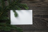 Fir branch with paper card on oak table from above — Stock Photo