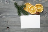 Spruce twig with dried orange slices and greeting card — Stock Photo