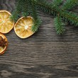 Spruce twig with dried orange slices on oak table — Stock Photo #57529509