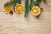 Christmas tree branch on oak table — Stock Photo