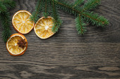 Spruce twig with dried orange slices on oak table — Stock fotografie