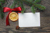 Spruce twig with red bow and orange slice — Stock Photo