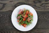 Salad with prosciutto arugula and tomatoes — Stock Photo