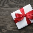 Gift box with red bow on wood table — Stock Photo #58571711