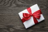 Gift box with red bow on wood table — Stock Photo