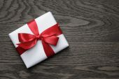 Gift box with red bow on wood table — Photo