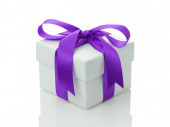 White gift box with purple ribbon bow — Stock Photo