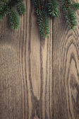 Fir branch on stained oak table from above — Foto Stock