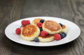 Homemade curd fritters on plate with berries — Stock Photo