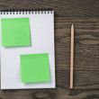 Notebook with pencil and sticky notes on oak wood table — Stock Photo #63043599