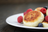 Homemade curd fritters on plate with berries — Stockfoto