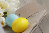 Easter eggs and white tulips on wood table — Stock Photo