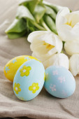 Handpainted easter eggs and white tulips on wood table — Stock Photo