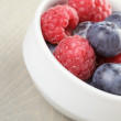 Blueberries and raspberries in bowl on wooden table — Stock Photo #67405765