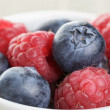 Blueberries and raspberries in bowl on wooden table — Stock Photo #67405767