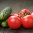 Ripe wet tomatoes on vine and cucumbers on wood table — Stock Photo #68694761