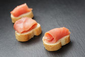 Baguette slices with curred salmon on slate background — Stock Photo