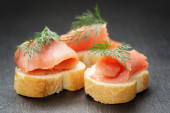 Baguette slices with curred salmon and dill on slate background — Stock Photo