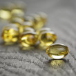 Heap of fish oil omega capsules on wooden table — Stock Photo #69398313