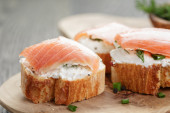 Baguette slices with smoked salmon and cheese cream on wooden table — Stockfoto
