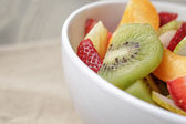 Fresh mix fruit salad with strawberry, kiwi and peach, on table — 图库照片