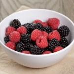 Ripe blackberries and raspberries in white bowl on old oak table, rustic — Stock Photo #71756719