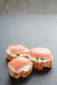 Small sandwiches with soft cheese and salmon on slate background — Stock Photo