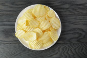 Rippled potato chips in white plate on wood table — Stock Photo