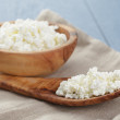Cottage cheese in wood bowl on blue wooden table — Stock Photo #72315521