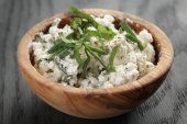 Fresh ricotta with herbs in olive wood bowl on old table — Stock Photo