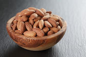 Roasted almonds in bowl on slate background — Stock Photo