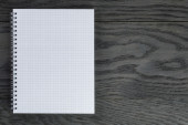 Blank notepad with chequered pages on gray wood table — Stock Photo