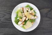 Caesar salad with chicken on oak table — Stock Photo