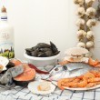 Assorted fresh fish and seafood on rustic table — Stock Photo #70703901